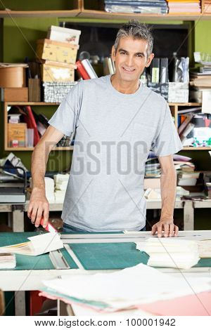 Portrait of confident mature male worker standing at table in factory