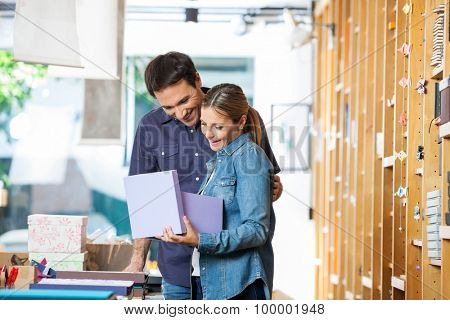 Surprised mid adult woman holding gift box while standing with man in store