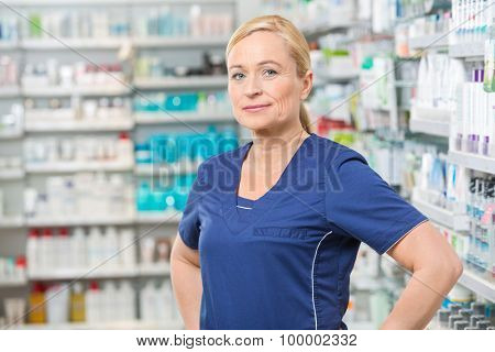 Portrait of confident female chemist smiling in pharmacy