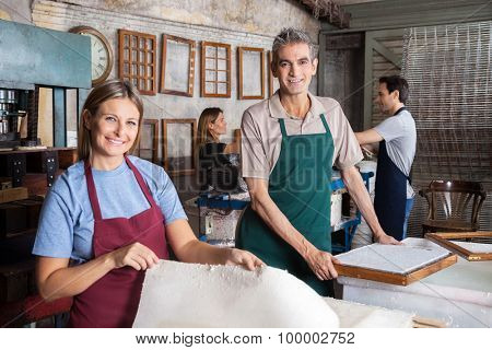 Portrait of happy male and female workers making papers in factory