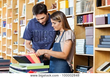 Mid adult female worker assisting male customer to choose envelop in shop