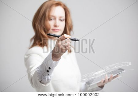 Young girl working with virtual screen on gray background