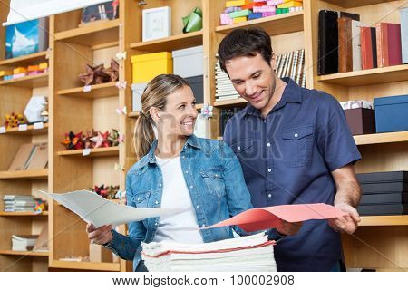 Smiling mid adult couple selecting papers in store
