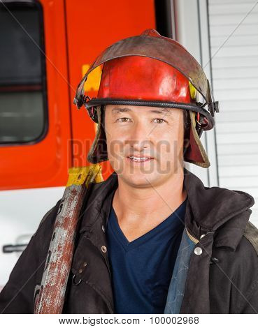 Portrait of confident male firefighter in red helmet standing against firetruck at station