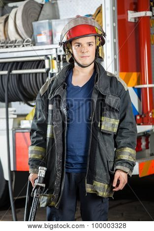 Portrait of confident firefighter holding hose against truck at fire station