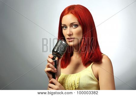 Beautiful young woman with microphone on gray background