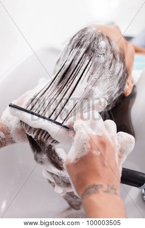 Beautiful young woman is getting a hairwash in salon