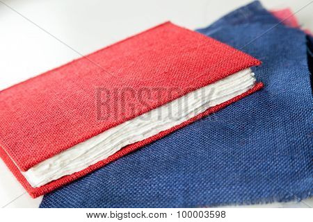 Closeup of fabric and red cover book on table in factory