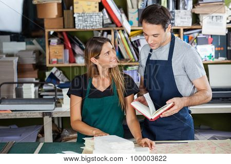 Mid adult female worker looking at colleague holding book in paper factory