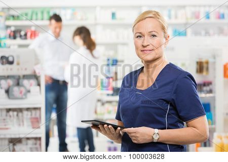 Portrait of confident assistant holding digital tablet while pharmacist and customer standing in background at pharmacy