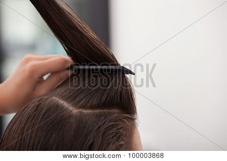 Skilled young hairstylist is serving her customer
