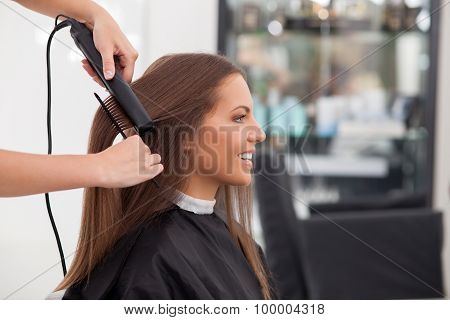 Experienced young hairstylist is serving her customer