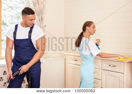 Attractive young cleaners are working together in a house