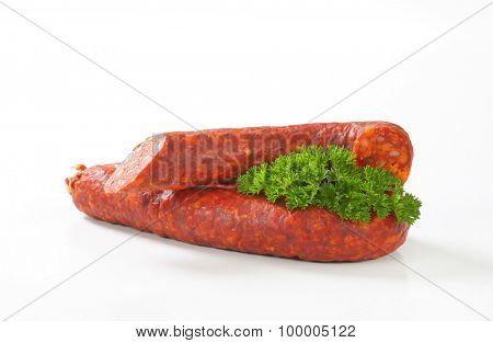spicy sausage and fresh parsley on white background