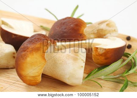 detail of boletus mushrooms with spice on wooden cutting board