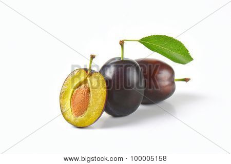 two and half ripe plums on white background