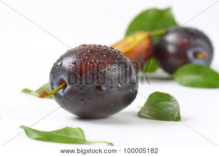detail of two and half washed plums on white background