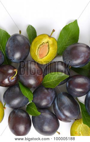 pile of ripe plums with leaves on white background