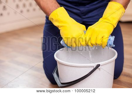 Cheerful young man is doing clean-up in his house