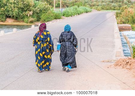 Two women in traditional attire crossing Draa river in Morocco