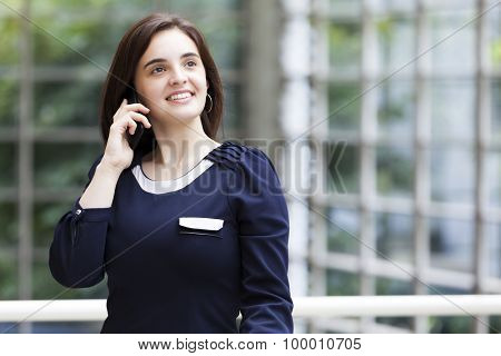Woman talking at the phone with modern building as background