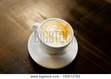 Closeup of a coffee cup on a dark table.