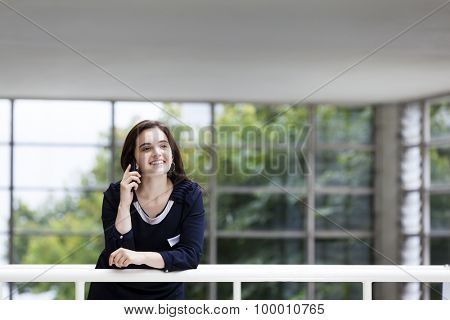 Business woman talking at the phone with modern building as background