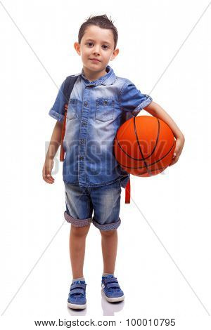 School boy posing with a basketball and backpack on white background