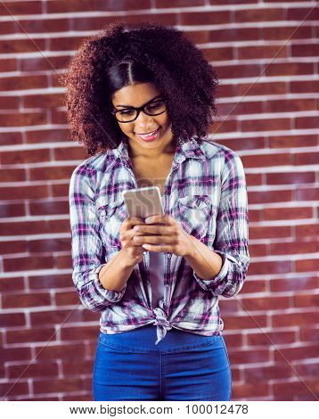 Smiling attractive hipster texting against red brick background