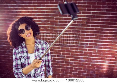 Attractive hipster taking selfies with selfiestick against red brick background