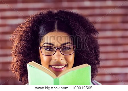 Portrait of attractive smiling hipster holding book against red brick background
