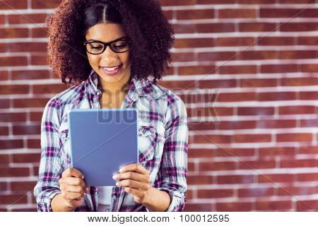 Attractive hipster smiling and looking at tablet against red brick background