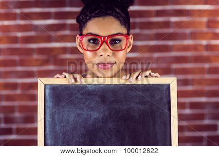 Portrait of a female hipster holding a blackboard against a brick wall