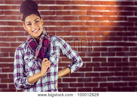Portrait of a beautiful smiling hipster against a red brick wall