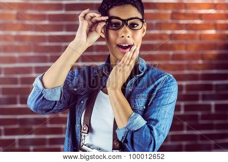 Portrait of a gorgeous hipster posing with glasses against red brick background