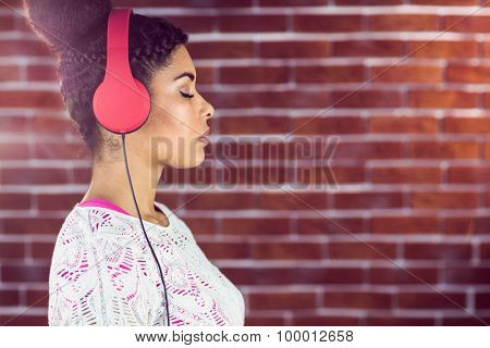 A beautiful woman concentrated on her music on a brick wall