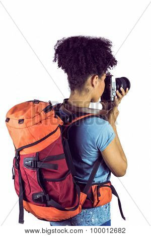 Young woman with backpack taking picture against a white background