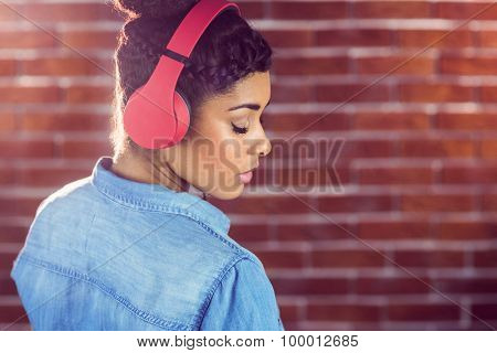 Pretty young woman with headphones looking back and leaning against a red brick wall