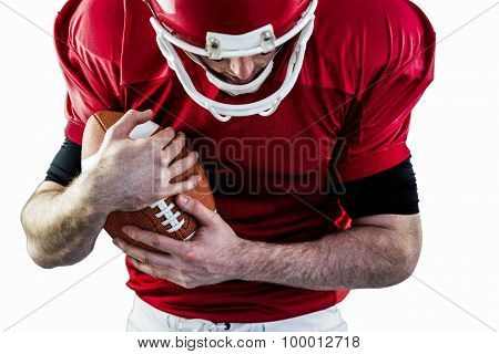 American football player protecting football against white background