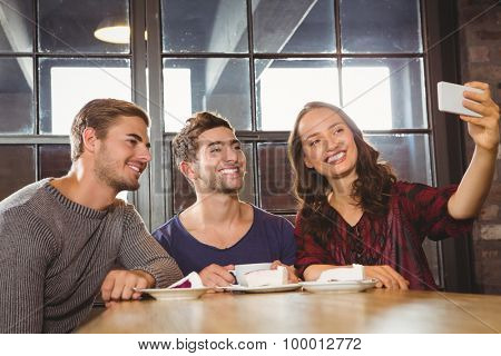 Smiling friends having coffee and taking selfies at coffee shop