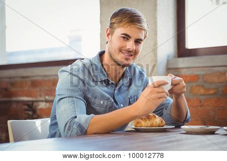 Portrait of handsome man enjoying coffee and croissant at coffee shop