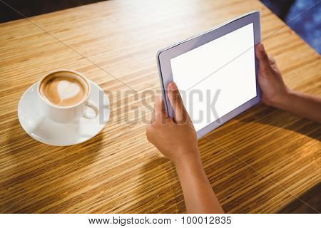 A businesswoman using a tablet and enjoying a coffee in a cafe