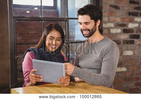 Couple looking at the tablet in a cafe