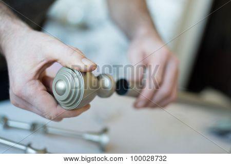 man gathers metal cornices. Close up