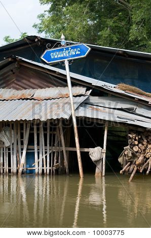 Road Sign In Flooded Village In Thailand