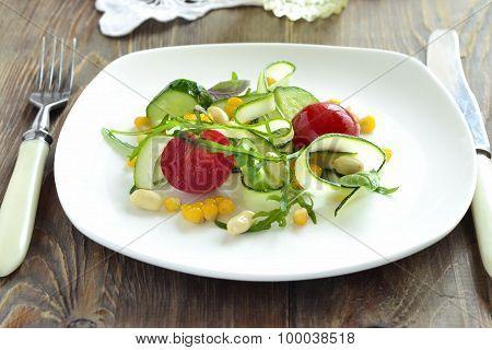 Salad with zucchini, arugula, corn, cucumbers and tomatoes