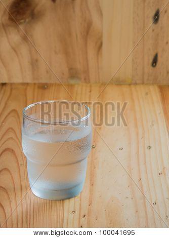 Water In Glass on wooden floor.