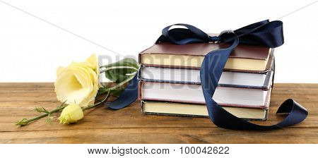 Stack of books with ribbon and flowers isolated on white