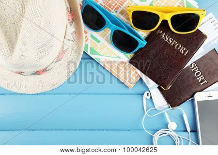 Sunglasses, passports, hats and map on color wooden background. Preparing for travel concept