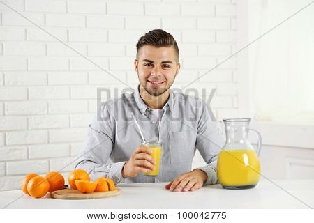 Young man showing glass of orange juice